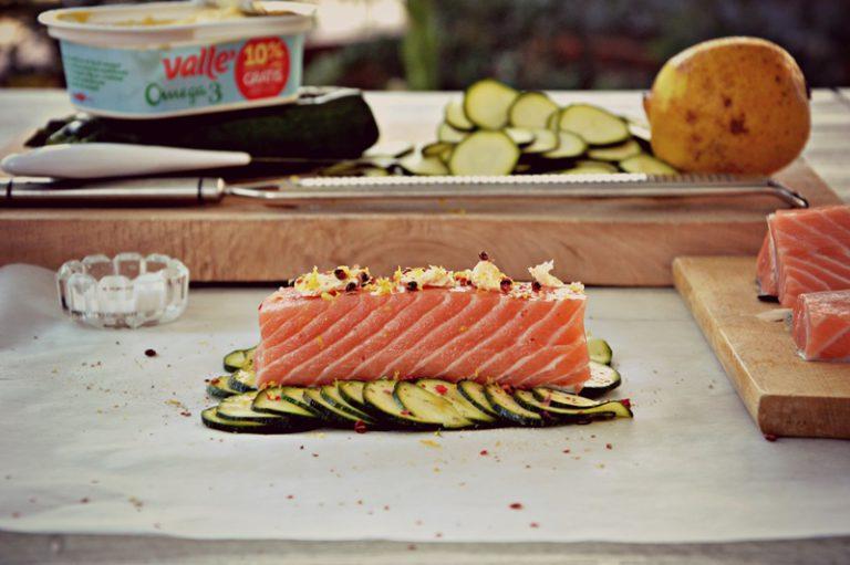 Appoggiate un trancio di salmone, salate e condite con 10 g di vallè e qualche grano di pepe rosa e la scorza del limone grattugiata.