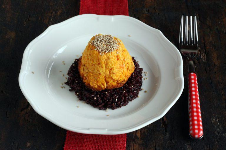 Nel mentre fate bollire il riso venere, scolatelo e saltatelo in una pentola in cui avrete preparato un soffritto di cipolla con le due carote.