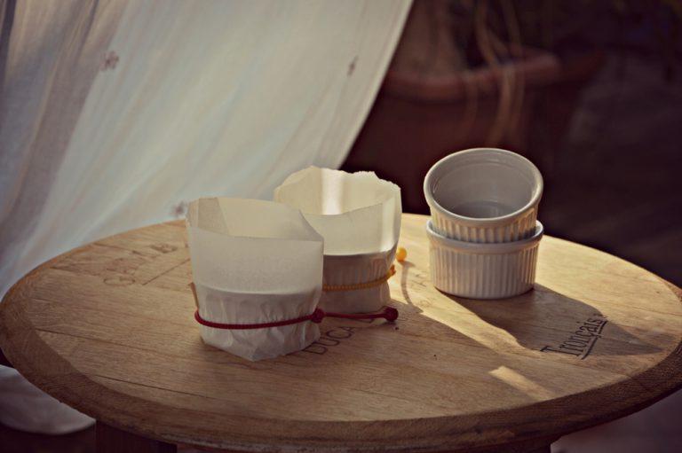 Fasciate 4 cocotte di porcellana (diametro 8 cm) con una striscia di carta forno, in maniera da rialzare il bordo della cocotte di circa 4 cm