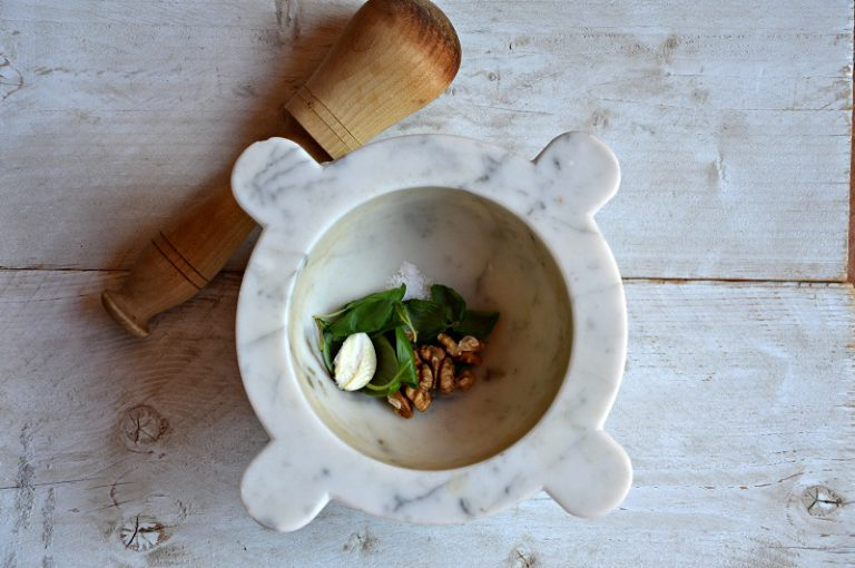 Pestate l'aglio degerminato con un po' di sale, il basilico e le noci, otterrete un miscuglio omogeneo che irrorerete con l'olio e insaporirete con una macinata di pepe.