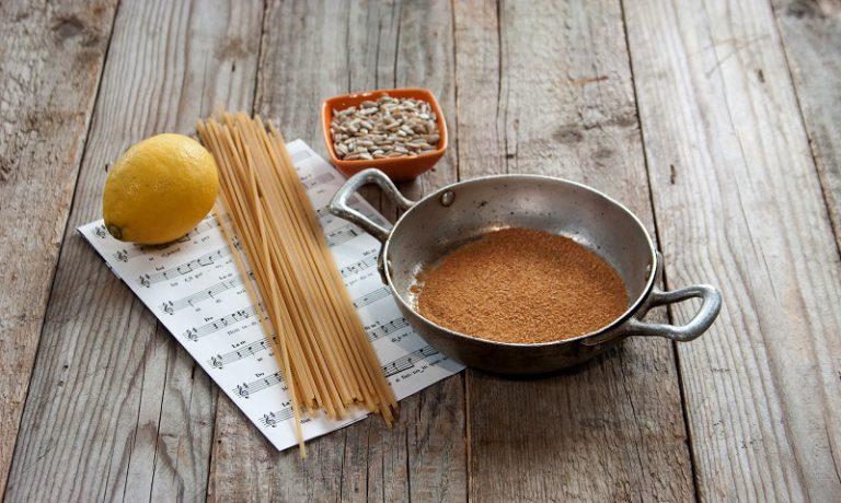 In un padellino tostate il pangrattato con due cucchiai di olio extravergine di oliva e un'acciuga sott'olio ben sgocciolata, grattugiate la scorza di mezzo limone biologico.