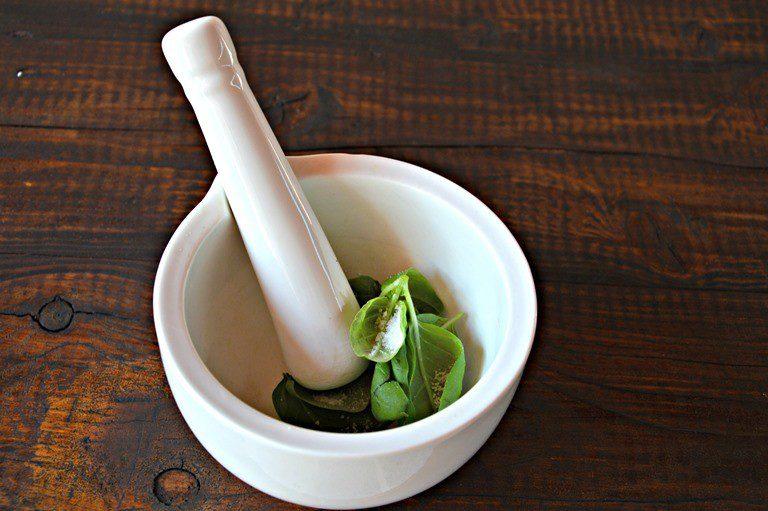 Pestate il basilico in un mortaio con un pizzico di sale, girate con il pestello, unite le mandorle