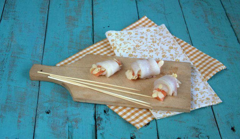 Arrotolate il salmone sulle striscioline di sogliola, ed infilatele su di uno spiedo.