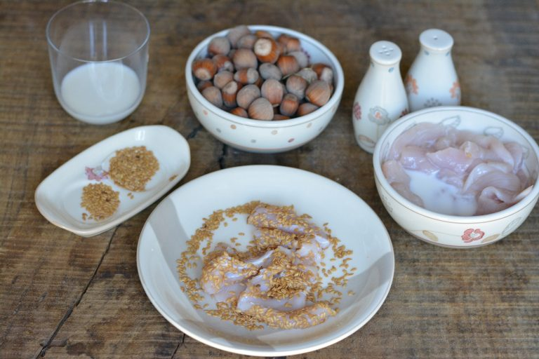 Passare gli straccetti di pollo nel latte e poi nei semi di lino, aggiungendo sale e pepe