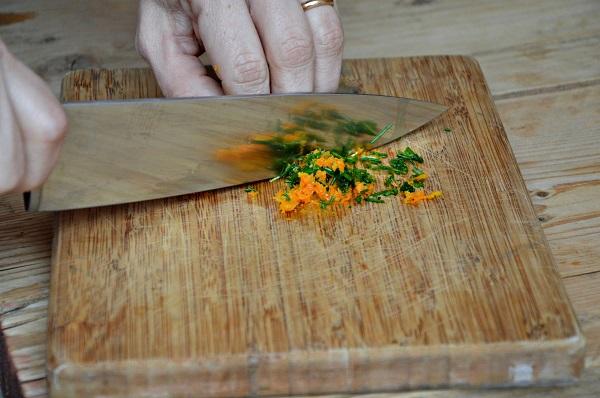 Grattugiate la scorza d'arancia. Tritate l'erba cipollina e mescolatela alla scorza, aggiungete qualche bacca di pepe rosa