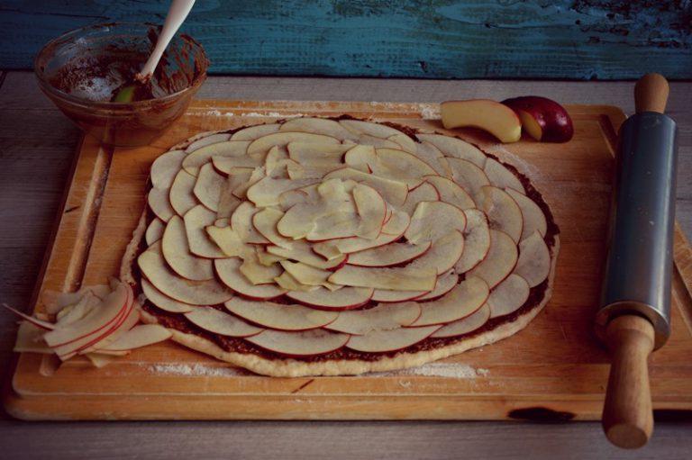 distribuite le fettine di mela tagliate sottilissime con una mandolina e arrotolate l'impasto lasciando la chiusura sul lato inferiore.