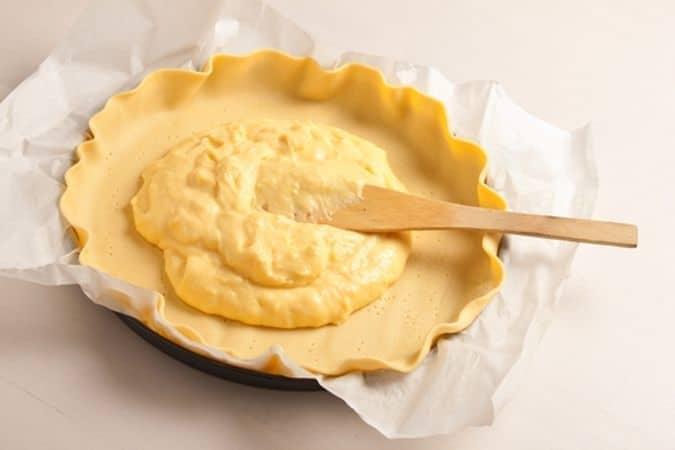 Stendi il primo rotolo di pasta frolla in una tortiera a bordi bassi, con il suo foglio di carta forno, bucherella il fondo con i rebbi di una forchetta e versa la crema pasticcera, livellandola con una spatola.