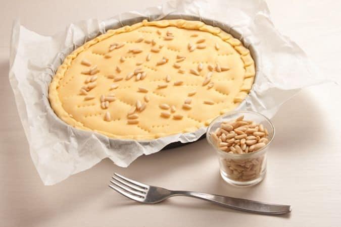 Ricopri con l'altro rotolo di pasta frolla, bucherella con la forchetta e distribuisci sulla superficie i pinoli.