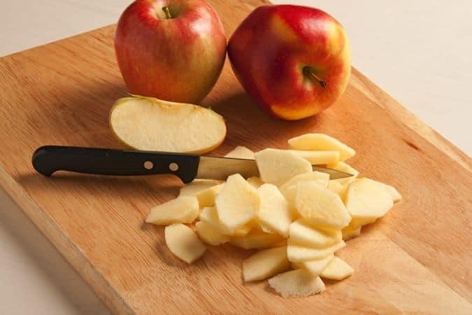 Taglia a spicchi le mele, elimina la parte di torsolo e sbucciali poi tagliali a fettine.