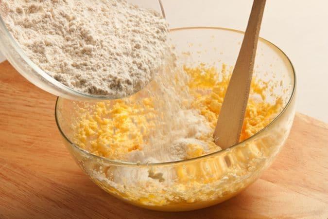 In una ciotola sbatti lo zucchero con i tuorli e la margarina, ammorbidita a temperatura ambiente; aggiungi, poca alla volta, la farina setacciata con il lievito e mescola bene per evitare la formazione di grumi.