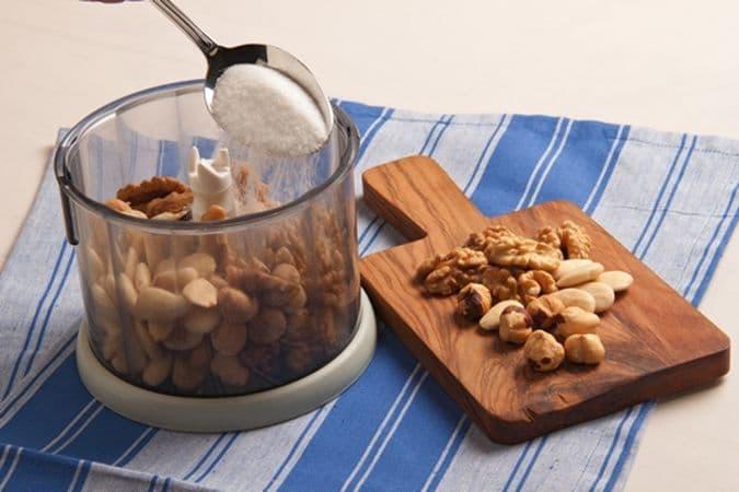 Metti nel mixer la frutta secca (tenendone da parte una manciatina) e frullala con lo zucchero