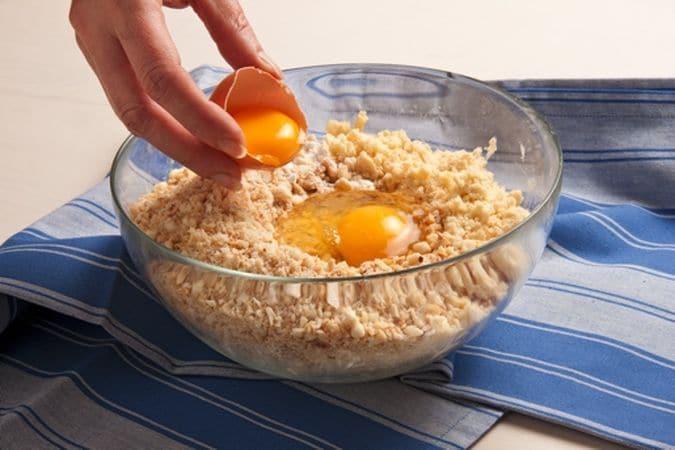 """fai un trito grossolano. In una ciotola lavora il burro con la farina 00, ottenendo un composto """"bricioloso"""", aggiungi la farina gialla, il trito di frutta secca, il lievito, un pizzico di sale, l'uovo e i tuorli."""