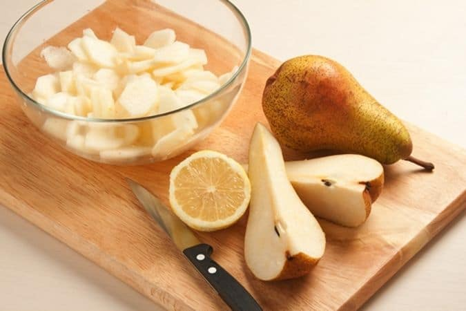 Taglia a spicchi le pere, sbucciale, privale del torsolo e tagliale a fettine; raccogli le fettine in una ciotola e irrorale con il succo di limone.