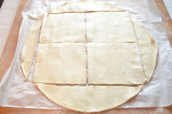 Stendete la pasta sfoglia su un piano di lavoro infarinato e ricavate un grosso quadrato che dividerete in 4 altri quadratini (come da foto). Impastate i ritagli e ricavate altri 2 quadrati della stessa grandezza  (all'incirca 10x10cm)