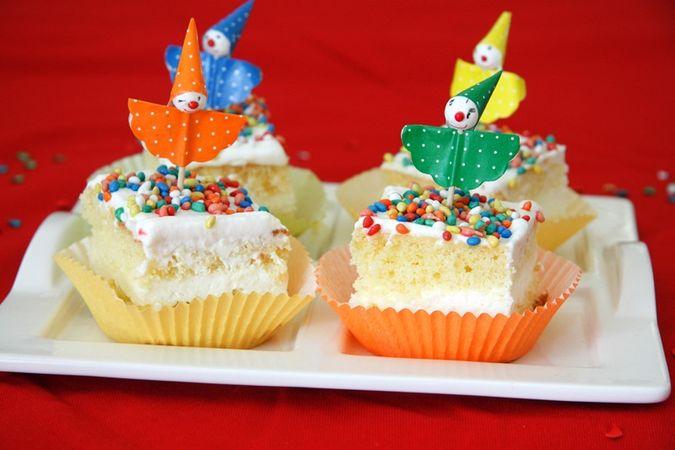 Tagliare la torta a metà per il senso della lunghezza e farcirla con la panna. Spalmare la panna della seconda ciotolina sulla superficie del dolce. Tagliarlo a quadretti e disporlo in pirottini colorati. Distribuire i confettini sulla superficie e decorare a piacere