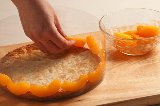 Cospargi entrambi con lo zucchero semolato e cuocili, nel forno preriscaldato a 200°, per 15-20 minuti.<br /> Fai ammollare la colla di pesce in acqua fredda, strizzala e falla sciogliere in un dl e mezzo dello sciroppo delle pesche su fuoco basso, aggiungi le pesche frullate e mescola bene; fai raffreddare il composto, mescolandolo spesso. Monta la panna ben fredda e mescolala delicatamente con la gelatina di pesche a temperatura ambiente. Disponi il disco senza decorazione sul piano di lavoro e circondalo con un anello di plastica semi rigida (oppure usa l'anello di uno stampo a cerniera, rivestito di carta forno); taglia a fettine tre mezze pesche sciroppate e disponile lungo tutto il perimetro, appoggiandole alla plastica.
