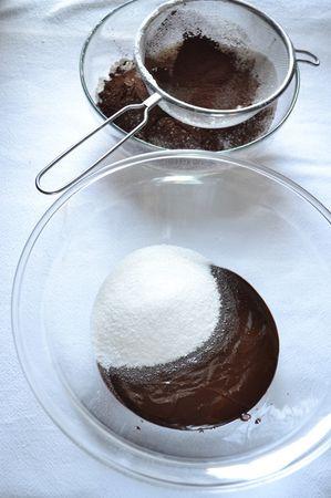 Versate lo zucchero e la margarina sciolti in una ciotola capiente e unite lo zucchero, mescolate e mettete da parte. In un'altra ciotola, setacciate la farina e il cacao e mescolate bene