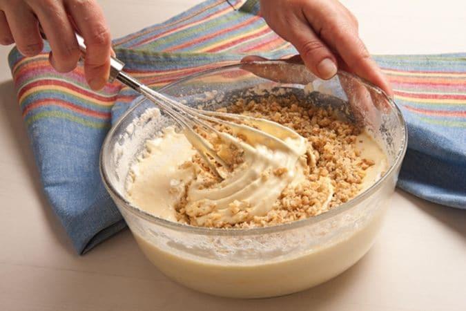 Torta di noci: aggiungere la granella di noci e versare il composto in una tortiera