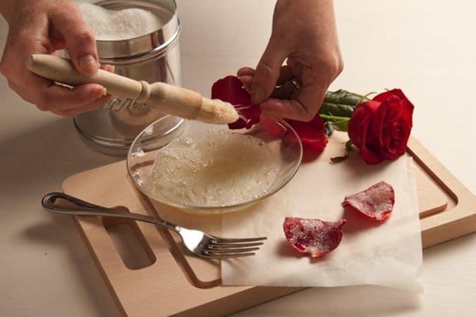 Quando la torta è pronta falla raffreddare poi ricoprila con il cioccolato fuso a bagnomaria e lascia asciugare. Spennella i petali di rosa con l'albume tenuto da parte (sbattuto appena con una forchetta) e cospargi con lo zucchero semolato;