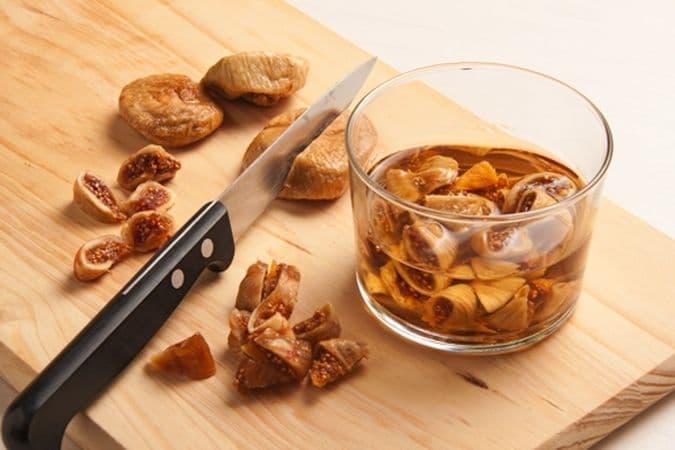Taglia a pezzetti i fichi secchi e mettili ad ammollare nel liquore per 15 minuti circa. Taglia a pezzetti anche i datteri, eliminando i noccioli.