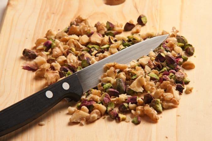 Trita grossolanamente le noci e i pistacchi poi mescola in una ciotola i fichi sgocciolati, i datteri, le noci e i pistacchi.