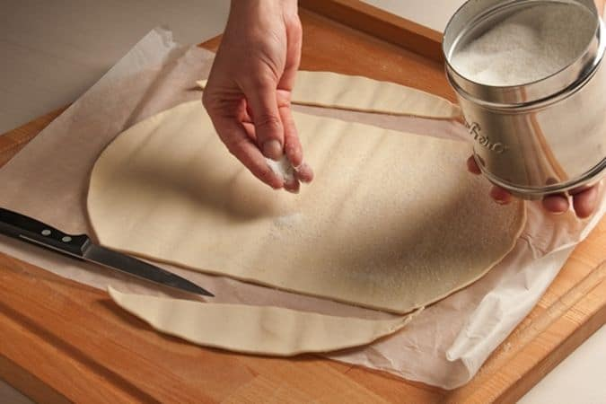 Srotola la pasta sfoglia, elimina due piccole strisce laterali per ottenere una forma più rettangolare, e cospargi la superficie con lo zucchero.