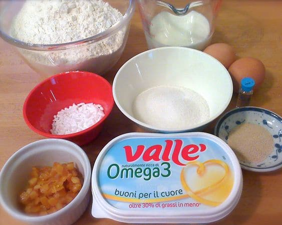 Fate intiepidire il latte, poi mescolatelo con 2 cucchiai di zucchero, 2 cucchiai di farina e il lievito; coprite e aspettate 15 minuti. Quando il lievito è fermentato, mescolatelo con la farina e il rimanente zucchero, poi aggiungete anche le uova leggermente sbattute, la margarina fusa e l'acqua di fiori d'arancio. Versate sulla spianatoia e impastate per almeno 5 minuti. Quando l'impasto è omogeneo ed elastico mettetelo in una ciotola larga unta di margarina, incidetelo a croce e coprite con pellicola trasparente. Mettete a lievitare in un luogo tiepido e riparato per un'ora