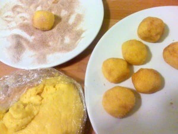 Trascorsa l'ora, mescolate lo zucchero di canna e la cannella in un piatto; prendete l'impasto, formate tante palline grandi come noci e rotolatele nello zucchero speziato, poi appoggiatele su un altro piatto. Mettete i biscotti in freezer per mezz'ora.