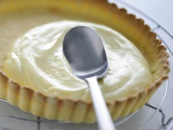 Monta la panna, elimina la scorza di limone dalla crema ed amalgamala con la panna montata. Versa la crema ottenuta nella base di pasta frolla, cospargila con i frutti di bosco e spolverizzali con lo zucchero al velo.Buon Appetito da Vallé