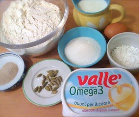 Togliete i semi da due capsule di cardamomo (se non siete abituati all'aroma non esagerate) e frantumateli in un mortaio o aiutandovi col fondo di un bicchiere. Fate intiepidire il latte, aggiungete un cucchiaio di zucchero, il lievito e coprite: aspettate 5 minuti finché il lievito inizia a fare la schiumetta