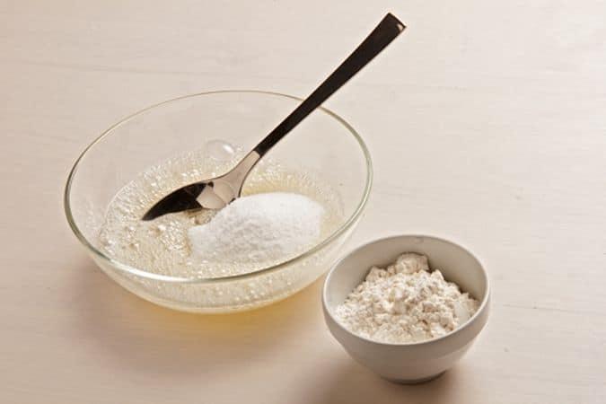 In una ciotola batti leggermente gli albumi con una forchetta, senza montarli, poi aggiungi lo zucchero, la farina e la margarina fusa.