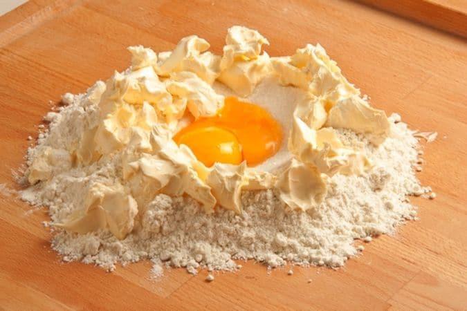 """Sulla spianatoia disponi la farina a """"fontana"""", aggiungi lo zucchero, i tuorli e la margarina a pezzetti."""