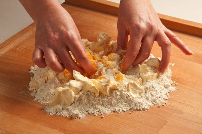 Comincia a impastare con la punta delle dita poi lavora bene l'impasto fino a renderlo uniforme, forma una palla, avvolgila di pellicola alimentare, e lascialo riposare in frigorifero per mezz'ora.