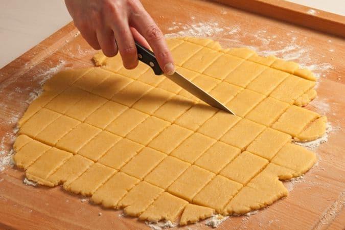 Trascorso questo tempo riprendi la pasta e stendila, sulla spianatoia leggermente infarinata, a uno spessore di quattro millimetri circa poi con un coltello tagliala a piccoli rettangoli regolari