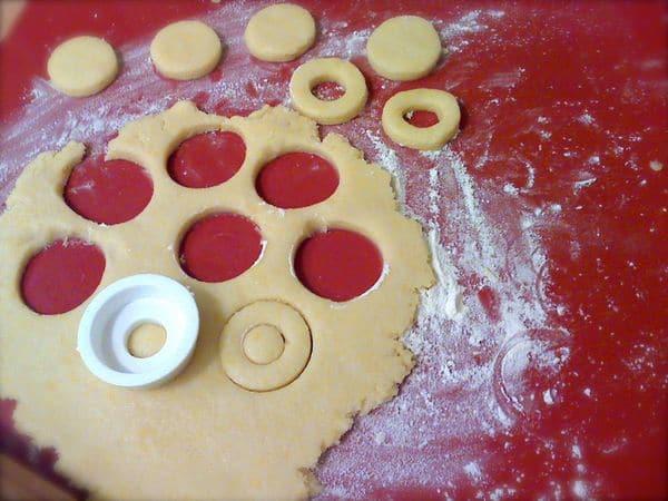 Accendete il forno a 180 gradi. Stendete l'impasto sulla spianatoia infarinata con uno spessore di 2-3 mm e ritagliate biscotti con e senza foro in ugual numero.