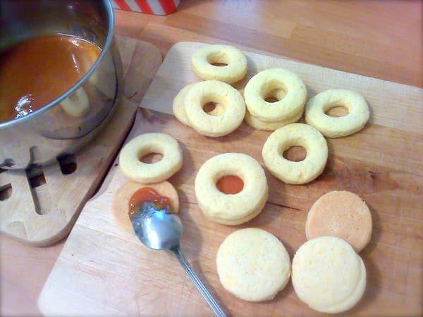 Mettete con delicatezza i biscotti sulla placca rivestita di carta forno e infornate per 15 minuti. Sfornate e fate raffreddare del tutto i biscotti, poi preparate la farcitura. Mettete la marmellata in un pentolino e fate scaldare a fuoco gentile mescolando in continuazione. Quando la marmellata è liquida, versatene un cucchiaino su ogni biscotto senza foro e coprite con la metà forata. Procedete fino a esaurimento biscotti.