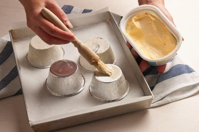 Spennella di margarina Vallé (quella che preferisci) l'esterno degli stampi e disponili, rivoltati, su una teglia rivestita di carta forno.