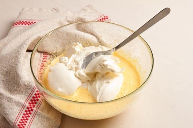 Sbatti i tuorli con lo zucchero e la scorza di limone, aggiungi il formaggio e la farina e diluisci con la panna e il succo di limone, mescolando bene per ottenere un composto uniforme. Monta a neve gli albumi e incorporali delicatamente al composto