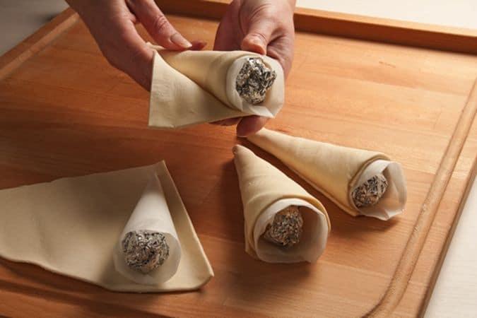 Dividi il rotolo di pasta sfoglia in 4 spicchi e arrotola ogni spicchio intorno a una delle basi preparate, sigilla bene la giuntura schiacciando con le dita.