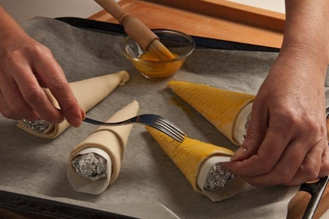 Disponi le cornucopie sulla placca del forno, rivestita con la carta forno, con la parte della giuntura rivolta contro la teglia. Spennella con l'uovo, leggermente sbattuto, la superficie delle cornucopie poi con i rebbi di una forchetta fai delle righe decorative e inforna a 200° per 10-15 minuti, sfornali quando cominciano a dorare e falli raffreddare.