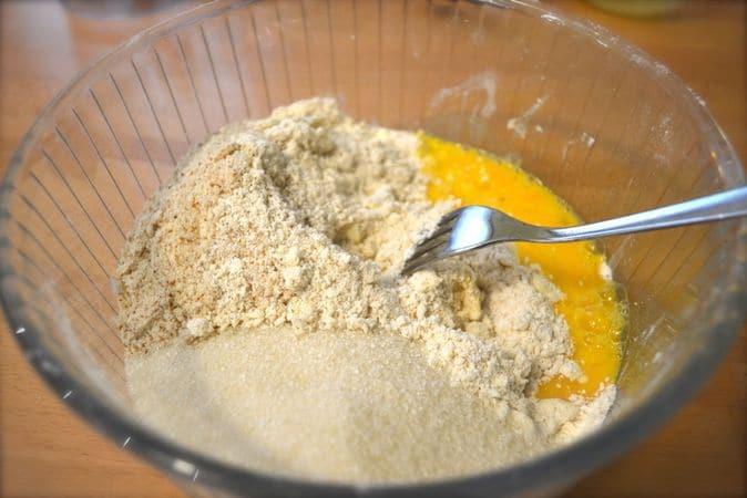 Mescolate le due farine e il lievito e setacciate in una ciotola larga. Tritate le mandorle in un mixer, sbattete leggermente l'uovo e aggiungete alle farine;  aggiungete 80 gr di zucchero e 125 gr di Vallé+Burro freddo