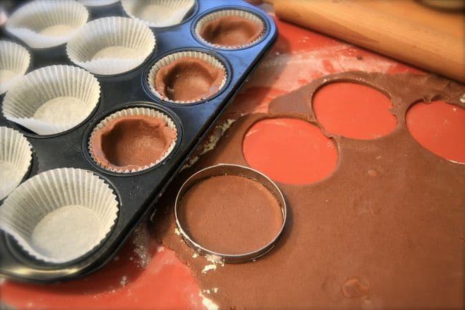 Accendete il forno a 200 gradi; lavate e asciugate con delicatezza i lamponi. Foderate uno stampo da 12 muffins con pirottini di carta. Stendete la pasta frolla al cacao e ricavate 12 tondi (7-8 cm di diametro) che userete per ricoprire il fondo di ogni stampino, premendo leggermente sui bordi per far prendere la forma dei pirottini