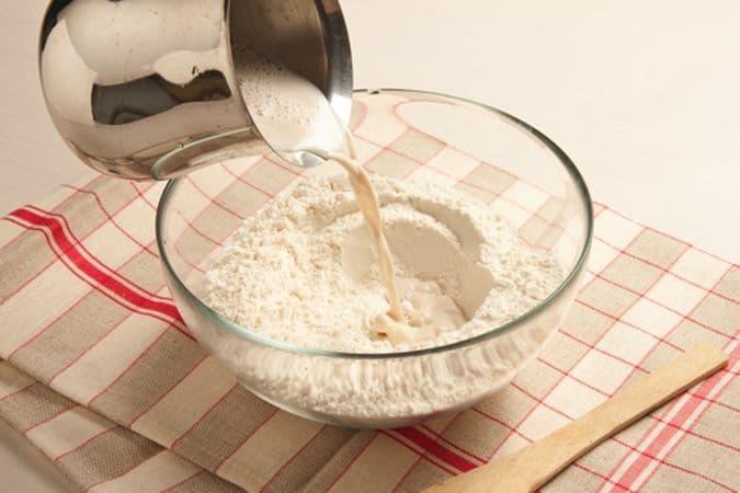 Versa la farina in una ciotola grande e unisci il latte tiepido nel quale avrai sciolto il lievito e lo zucchero, lavora il composto fino a renderlo uniforme poi lascialo lievitare, in un luogo tiepido, per 20 minuti.