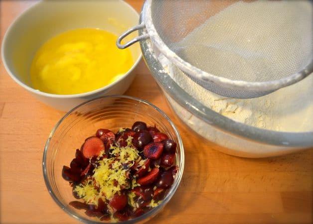 Accendete il forno a 200 gradi; rivestite uno stampo da 12 muffin con pirottini di carta. Lavate e tagliate a pezzettini le ciliegie. Unite farina e lievito, mescolate bene e setacciate. Fate sciogliere la margarina a bagnomaria o nel microonde. Grattugiate la scorza di limone e unitela alle ciliegie