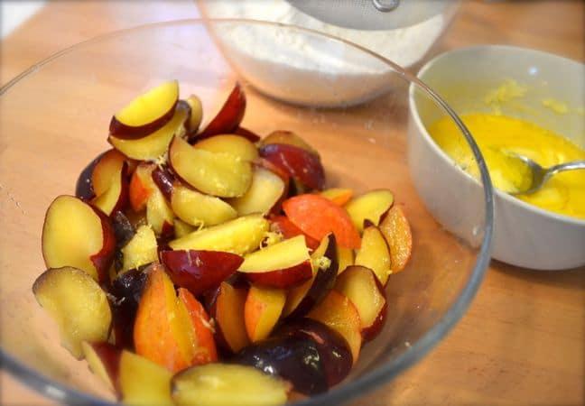Accendete il forno a 180 gradi; Unite farina e lievito e setacciate. Sciogliete la margarina a bagnomaria o nel microonde e lasciate raffreddare un poco. Lavate le susine, tagliatele a spicchi, unite la scorza di limone grattugiata e irrorate col succo di limone