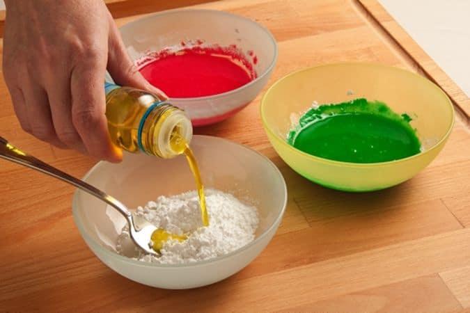 """Nel frattempo metti qualche cucchiaio di zucchero a velo in diverse ciotoline (una per ogni colore che hai deciso di usare) e aggiungi il colorante, mescola con cura fino ad ottenere un composto fluido ma non troppo liquido, altrimenti la glassa tenderà a """"scivolare""""."""