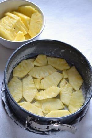 Foderate il fondo di una tortiera a cerchio rimovibile (22 cm diametro) con carta forno e ungete i bordi. Distribuite i 2 cucchiai di zucchero sul fondo e coprite con uno strato di fettine d'ananas.