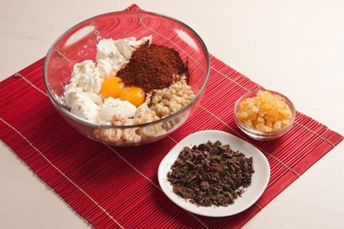 In una ciotola mescola la ricotta con il grano cotto, i tuorli, lo zucchero e il cacao.