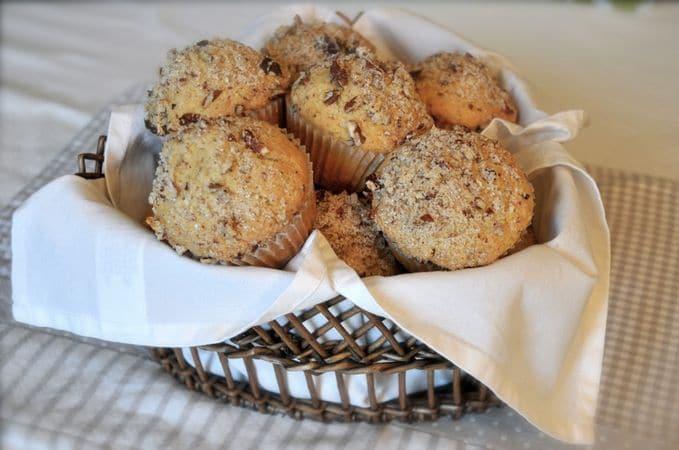Dividete l'impasto in 12 stampini da muffins che avrete rivestito con pirottini (riempiteli fino all'orlo). Tritate le noci in modo grossolano, mescolatele con lo zucchero di canna e distribuite questo composto sui muffins