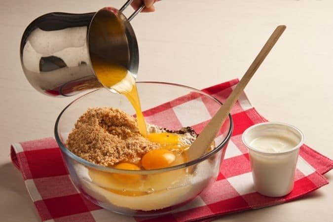 Metti in una ciotola la farina e mescolala con il lievito ed il cacao, aggiungi la granella di nocciole (tenendone da parte 2 cucchiai) lo zucchero, le uova, lo yogurt e la margarina fusa; mescola bene fino a ottenere un composto uniforme.